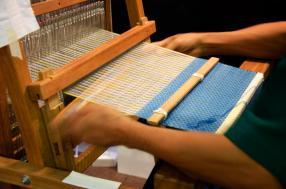 povos-tailandeses-que-usam-o-tear-ou-máquina-de-tecelagem-pequena-para-mostra-de-tecelagem-85547773