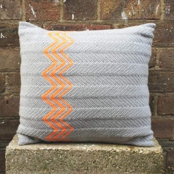 almofada-de-crochê-cinza-com-detalhes-geométricos-laranja